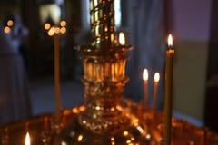 Lite brännande kyrkastearinljus mot en mörk bakgrund, closeup Arkivbild