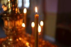 Lite brännande kyrkastearinljus mot en mörk bakgrund, closeup Fotografering för Bildbyråer