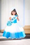 Lite brud. En flicka i en frodig vit- och blåttbröllopsklänning Arkivbild