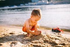 Lite bygger pojken diagram av sand på flodbanken på solnedgången dagen, händer gör former från våt sand Fotografering för Bildbyråer