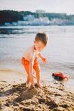 Lite bygger pojken diagram av sand på flodbanken på solnedgången dagen, händer gör former från våt sand Royaltyfri Bild
