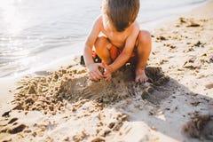Lite bygger pojken diagram fr?n sanden p? kusten av dammet p? solnedg?ngen av dagen, h?nder gr?ver upp sanden i knaprigt plan royaltyfria bilder