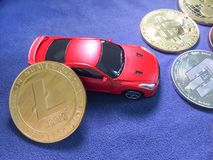 Lite coin lean agianst car model and others crypto coin on blue Royalty Free Stock Photo