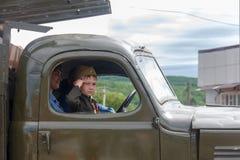 lite deltar pojken i form av en sovjetisk soldat i cockpiten av en armébil i en ståta i heder av segerdagen royaltyfri bild