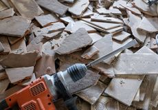 Demolition work with a demolition hammer. A lite demolition hammer lies on a pile of broken tiles Royalty Free Stock Photos