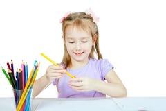 Lite drar flickan Hon rymmer en blyertspenna och ler royaltyfri bild