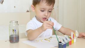 Lite drar pojken teckningar på ett vitt ark av papper, med gouachemålarfärger Närbild lager videofilmer