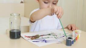 Lite drar pojken vattenfärgteckningar på ett vitt ark av papperssammanträde på en tabell stock video