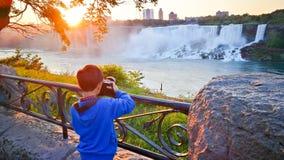 Lite filmar pojken morgonsolen av Niagara Falls arkivfoton