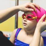Lite flicka av bärande skyddsglasögon för europeiskt utseende i pölen royaltyfri bild