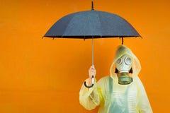 Lite flicka i en gasmask på en regnig dag Arkivbild