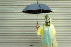 Lite flicka i en gasmask på en regnig dag Royaltyfria Foton
