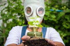 Lite flicka i en gasmask som rymmer en planta fotografering för bildbyråer