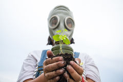Lite flicka i en gasmask som rymmer en planta Royaltyfri Bild