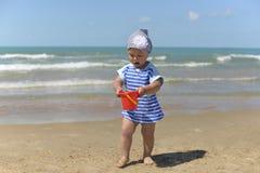 Lite flicka i en halsduk som spelar på den sandiga stranden arkivbild