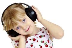 Lite flicka med hörlurar som lyssnar till musik Arkivfoto