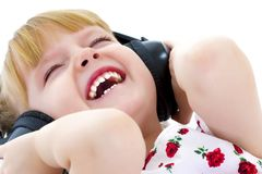 Lite flicka med hörlurar som lyssnar till musik Arkivbilder