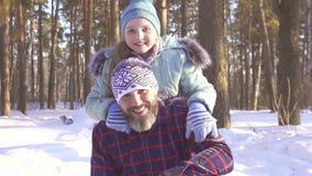 Lite flicka med hennes kasta för fader som är insnöat vinterskogen stock video