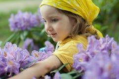 Lite flicka på ljusa blommor och att tycka om för lilor deras lukt Royaltyfri Fotografi