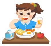 Lite flicka som är lycklig att äta frukosten i morgonen