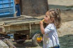 Lite flicka som äter en apelsin i en marknad royaltyfri bild