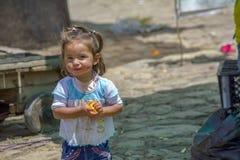 Lite flicka som äter en apelsin arkivfoton