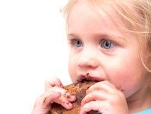 Lite flicka som äter en kaka royaltyfria bilder