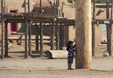 Lite flicka som förutom spelar det norr huset av den Taos puebloen royaltyfria bilder
