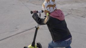 Lite flicka som rider en sparkcykel längs vägen längs stranden stock video