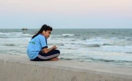 Lite flicka som sitter och ser havet arkivfoton