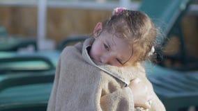 Lite flicka som slås in i en handduk, med en smutsig framsida, ensamt sammanträde på sammanträde på en soldagdrivare av pölen, i arkivfilmer