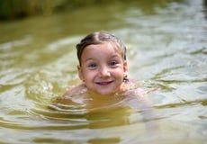 Lite flicka som spelar i en sjö Royaltyfri Bild