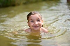 Lite flicka som spelar i en sjö Royaltyfri Fotografi