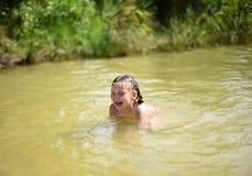 Lite flicka som spelar i en sjö Arkivfoto