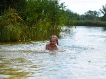 Lite flicka som spelar i en sjö Royaltyfria Foton