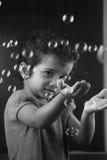 Lite flicka som spelar med bubblor Arkivfoton