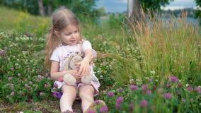 Lite flicka som spelar med en leksakkanin i ängen bland blomningväxten av släktet Trifolium lager videofilmer