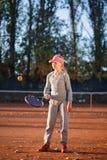 Lite flicka som står på spelplanen och stoppar en boll om en tennisracket Royaltyfri Bild