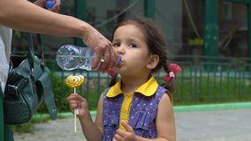 Lite flickadrinkar från en plast- flaska lager videofilmer