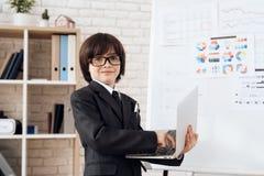 Lite framlägger sig pojken i exponeringsglas och dräkt som en affärsman Denhaired pojken spelar en rikeman arkivfoton
