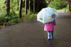 Lite går flickan på en regnig dag royaltyfria foton