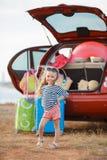 Lite går flickan på en resa på en röd bil Arkivfoto