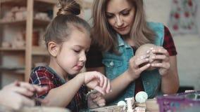 Lite gör flickan en lera att tillverka i ett krukmakeriseminarium Mamman och barnet spenderar tid som gör tillsammans idérikt arb lager videofilmer