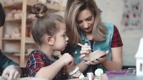 Lite gör flickan en lera att tillverka i ett krukmakeriseminarium Mamman och barnet spenderar tid som gör tillsammans idérikt arb stock video