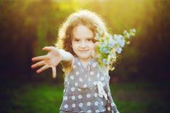 Lite ger flickan en bukett till hans moder eller fader Mum Dad arkivfoto