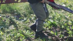 Lite gräver pojken jordningen med en skyffel och växter ett träd arbeta i trädgården fjäder lager videofilmer