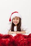 Lite grinar julflickan med ett stort Arkivbild