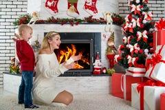 Lite grundar pojken och hans moder många julklappar på trädet Glad jul och lyckliga ferier! Royaltyfri Foto