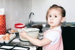 Lite gullig flicka som hemma f?rbereder degen i k?ket arkivbild