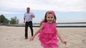 Lite härlig flicka som kör med hennes farfar på stranden Flickan kör på förgrunden, farfadern in stock video